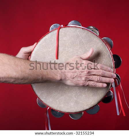 A tambourine being played isolated against a red background in the square format with copy space. - stock photo