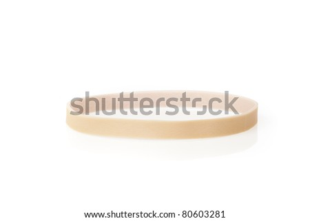 A tan rubber band against a white background - stock photo