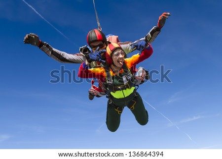 A tandem jump instructor and a passenger in a free fall. - stock photo