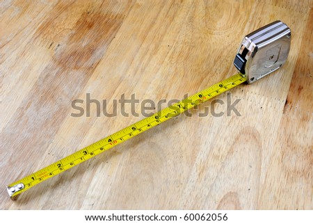 A tape measure extended on a wooden tabletop. - stock photo