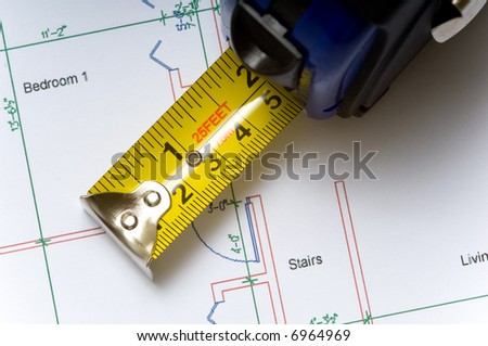 A tape measure slightly open lying on top of a house floor plan, construction industry or real estate