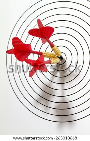 A target has been hit by three darts in the center. - stock photo