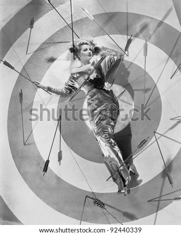 A target of desire, a young woman lying on the bulls eye with arrows around her - stock photo