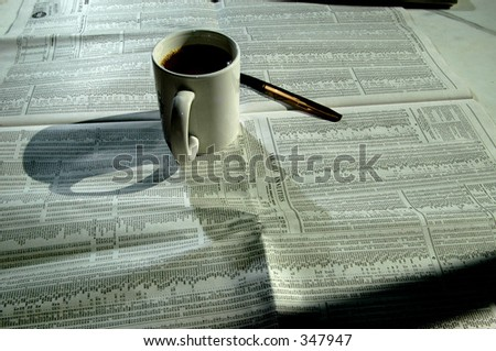 a tasty cup of coffee with the stock charts and a gold pen - stock photo