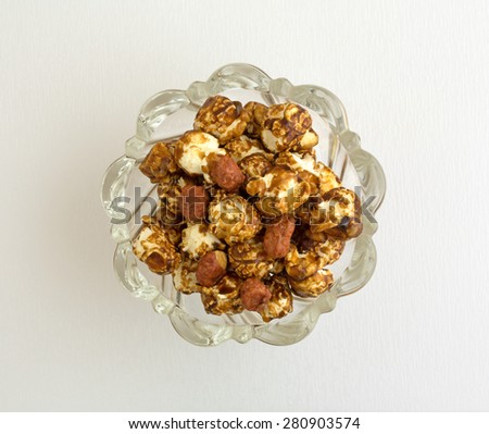 A tasty dish of caramel coated popcorn with peanuts on a white background. - stock photo