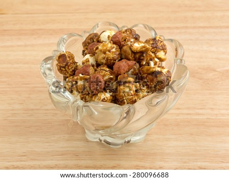 A tasty dish of caramel coated popcorn with peanuts on a wooden counter top. - stock photo