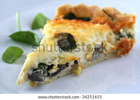 A tasty slice of spinach quiche (shallow DOF) - stock photo