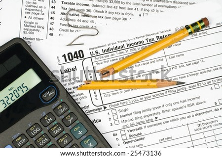 A tax form, calculator, broken pencil and bent paper clip shot the frustration of filing taxes