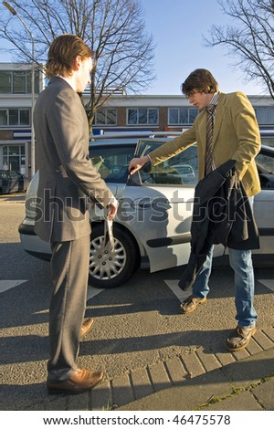 A Taxi driver opening the rear door for a customer - stock photo