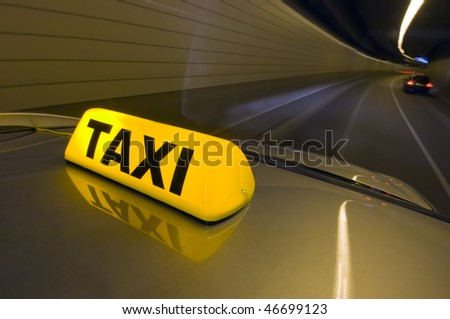 A taxi driving at high speed through a tunnel,  overtaking other cars - stock photo