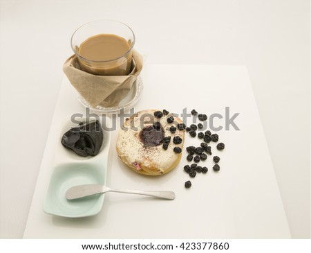 A tea set comprises  a round shaped blueberry jam doughnut glazed with sugar icing and a glass of latte. Garnished with some dried blueberries. Isolated on white background. - stock photo