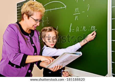A teacher and her student during class at school. Education. - stock photo