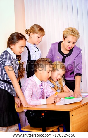 A teacher and her students during class at school. Education.