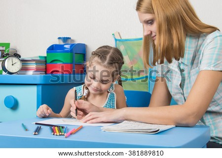 A teacher helps a five-year girl with a ruler to draw - stock photo