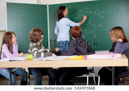 A teacher in chemistry class analyzing formulas on a blackboard - stock photo