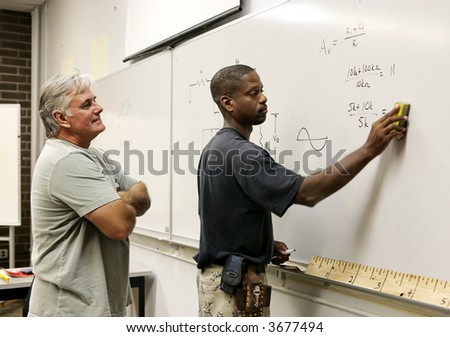 A teacher looks on as his adult education student erases the board. - stock photo