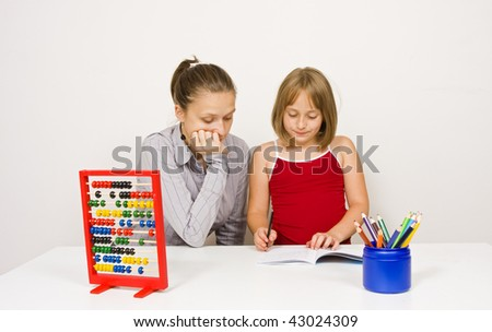 A teacher, or mother, learning together with her student, or daughter, paying attention to the little girl's action agains white wall - learning tools and educational objects on table. - stock photo