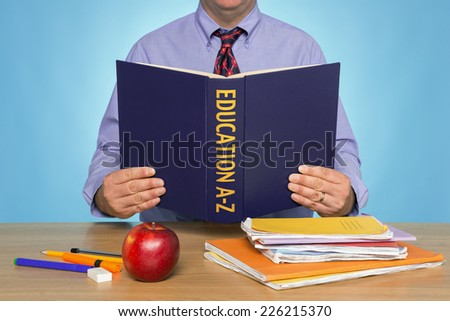 A teacher sat at a desk reading an EDUCATION A-Z book. - stock photo