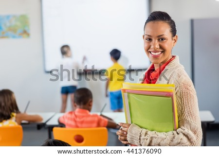 A teacher smiling at camera in classroom - stock photo
