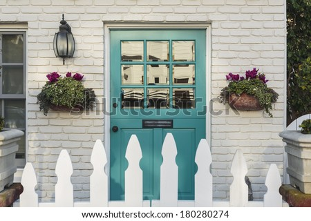 A teal wooden front door to a home, with white picket fence gate in foreground. The door is framed by two flower planters, and detail of the white, brick house.  - stock photo