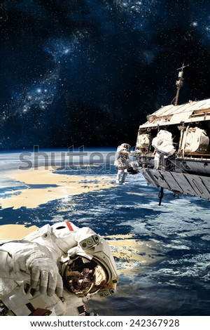A team of astronauts perform work on a space station while orbiting a large, Earth-like planet. A large star forming nebula is in the background. Elements of this Image Furnished by NASA. - stock photo