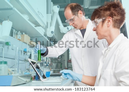 A Team of chemists are analyzing an alga liquid and comparing it with the saved value from the mobil device. - stock photo