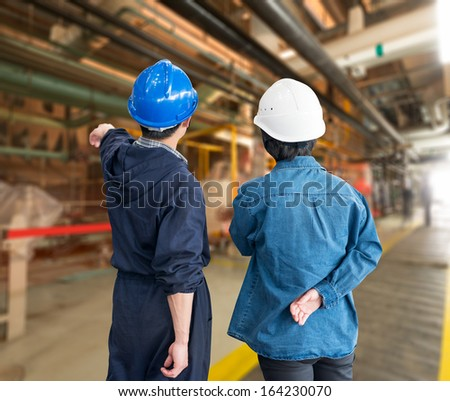A team of construction workers with helmets at work place in a factory