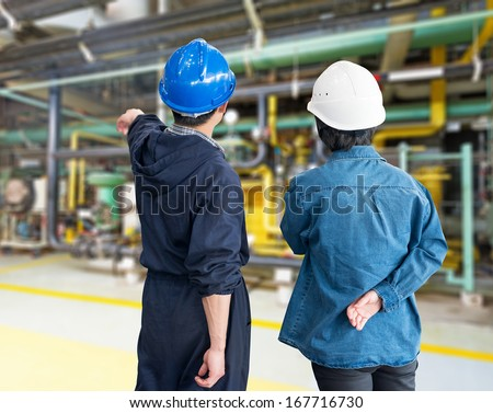 A team of construction workers with helmets at work place in a factory - stock photo