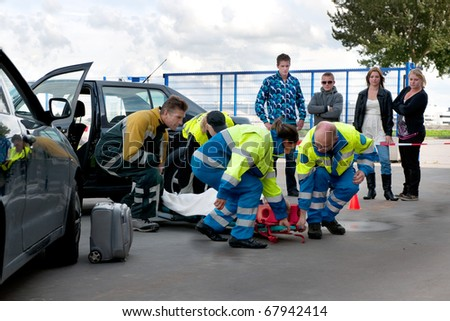 A team of emergency medical services at work, lifting an injured woman on a stretcher, to carry her away - stock photo