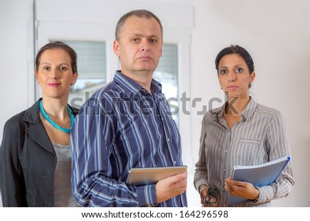 A team of happy businesspeople holding  documents and laptop - stock photo