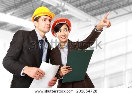 A team of male and female architect pointing at construction site - stock photo