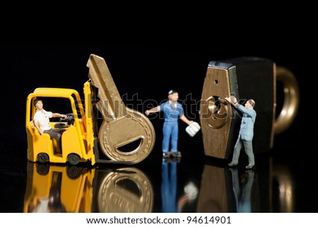 A team of miniature model workmen offloading a key and padlock from a forklift to enhance security - stock photo