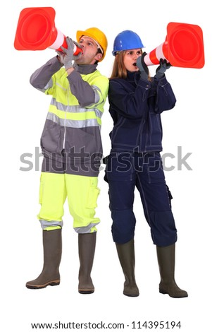 A team of tradespeople yelling into pylons - stock photo
