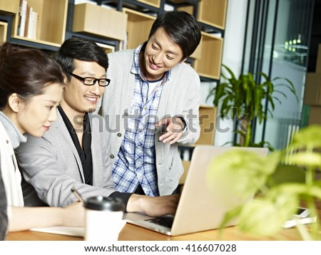 a team of young asian business people working together using laptop computer in office. - stock photo