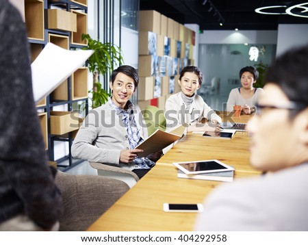 a team of young asian entrepreneurs meeting in office discussing ideas for new business. - stock photo