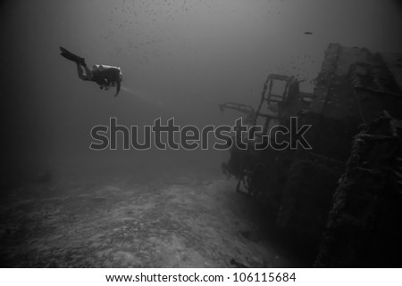 A technical diver swimming alongside of an underwater shipwreck laying on its side. The USCG Bibb is an artificial reef inside the John Pennekamp State Park in Key Largo, Florida. - stock photo