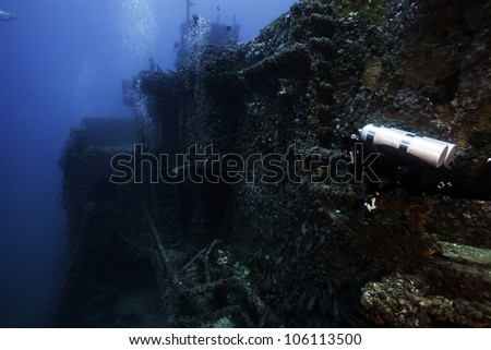 A technical female diver swimming alongside the USCG Duane. A sunken shipwreck in the John Pennekamp State Park in Key Largo, Florida. - stock photo