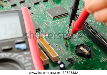 A technician testing a motherboard using multimeter - stock photo