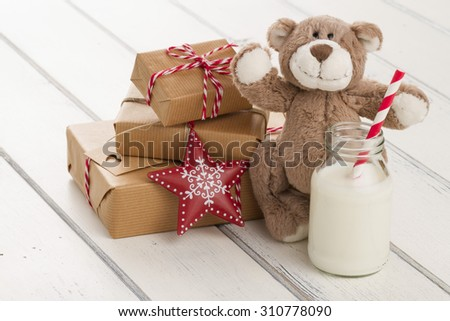 A teddy bear, a red star and a school milk bottle with a straw on a white wooden table. some paper parcels (christmas gift boxes) wrapped with paper kraft and tied with red & white baker's twine. - stock photo
