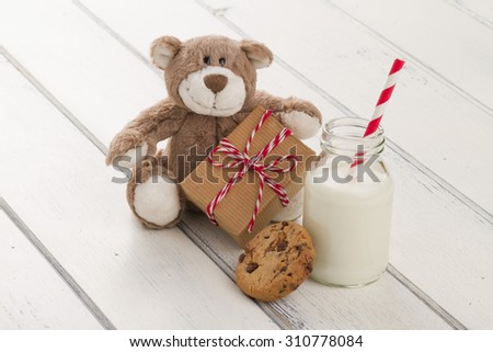 A teddy bear with a paper parcel wrapped with paper kraft and tied with red & white baker's twine. A chocolate chip cookie and a school milk bottle with a straw on a white wooden table - stock photo