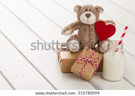 A teddy bear with a red heart. Two paper parcels (christmas gift boxes) wrapped with paper kraft and tied with red & white baker's twine. A school milk bottle with a straw on a white wooden table - stock photo