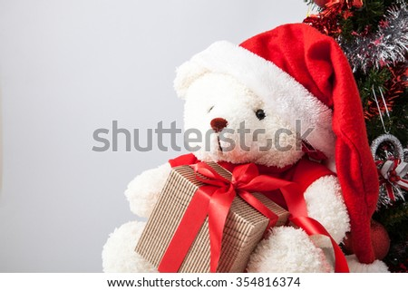 A teddy bear with gifts for christmas, dressed as santa claus and Christmas decoration.