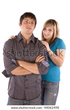 A teen boy standing with a smirk on his face while his girlfriend has a big smile on her face.