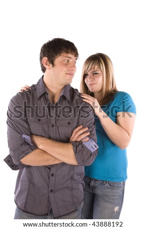 A teen boy standing with a smirk on his face while his girlfriend is giving a dirty look.