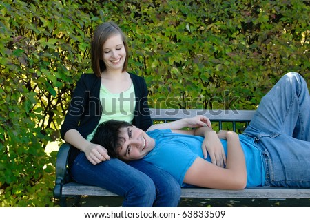 A teen boyfriend lying on his girlfriend's lap - stock photo
