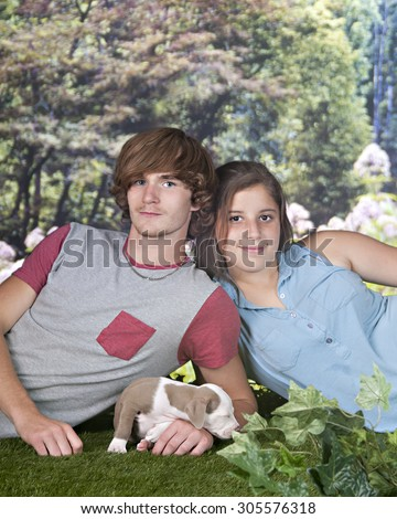 A teen couple relaxed together on a lawn looking up from playing with a young pitbull puppy. - stock photo