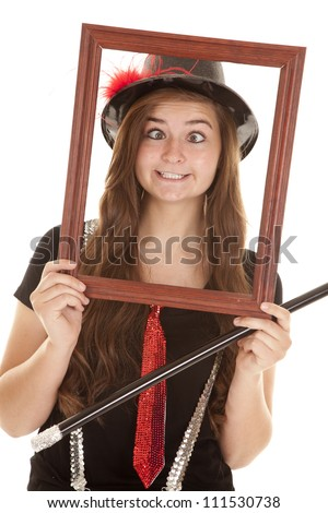 a teen girl holding a picture frame up by her face giving a funny expression. - stock photo