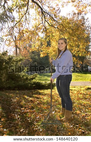 A teen girl just starting to rake fall leaves.