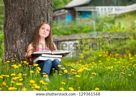 A teen-girl reads a book in the meadow.