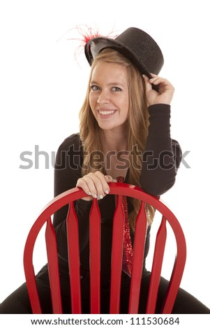 A teen girl sitting on a red chair holding on to her top hat with a smile on her face. - stock photo